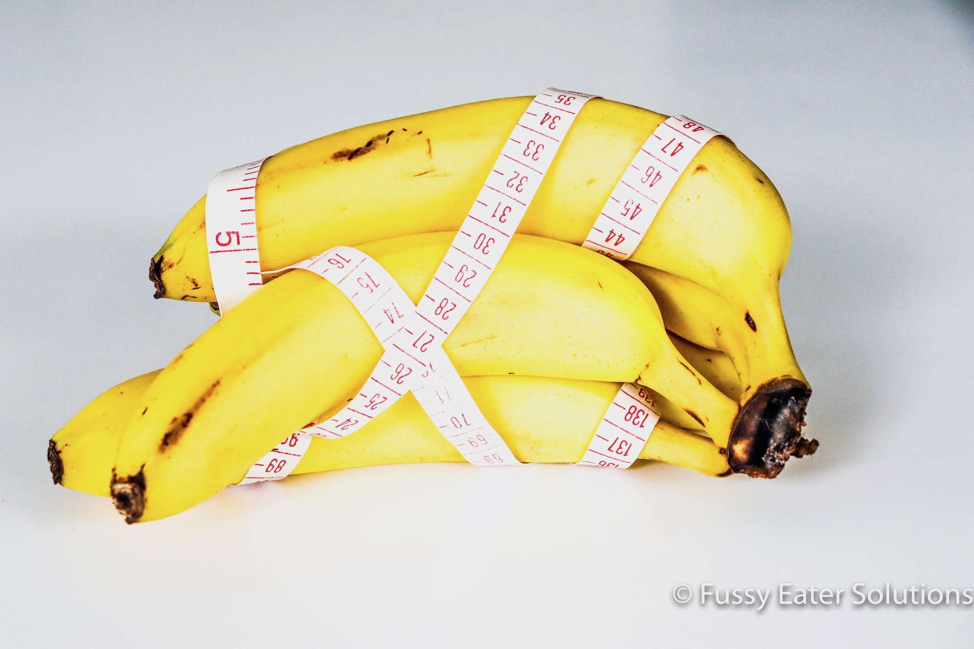 Bananas wrapped in measuring tape to suggest dieting